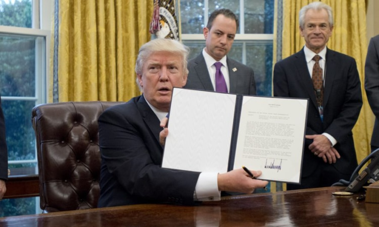"Donald Trump Signs Three Executive Orders - United States President Donald Trump shows the Executive Order withdrawing the US from the Trans-Pacific Partnership (TPP) after signing it in the Oval Office of the White House in Washington, DC on Monday, January 23, 2017. The other two Executive Orders concerned a US Government hiring freeze for all departments but the military, and ""Mexico City"" which bans federal funding of abortions overseas. Standing behind the President, from left to right: US Vice President Mike Pence; White House Chief of Staff Reince Preibus; Peter Navarro, Director of the National Trade Council; and Jared Kushner, Senior Advisor to the President. Credit: Ron Sachs / Pool via CNP /MediaPunch/IPX"